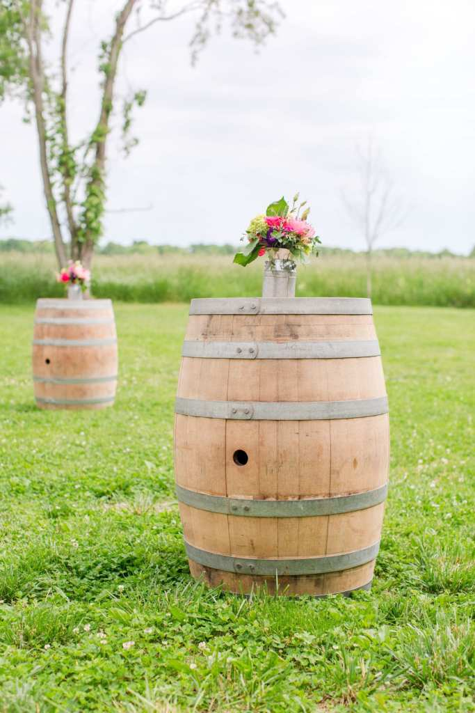 small floral arrangement in a metal milk jug on top of wooden wine barrels set up throughout the cocktail hour area outside of the barn at the Updike Farmstead