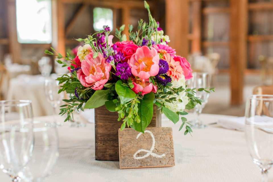 close up of small reception floral arrangement of multicolored wildflowers, roses, peonies in a small wooden box with wooden table numbers by the Flower Shop of Pennington Market