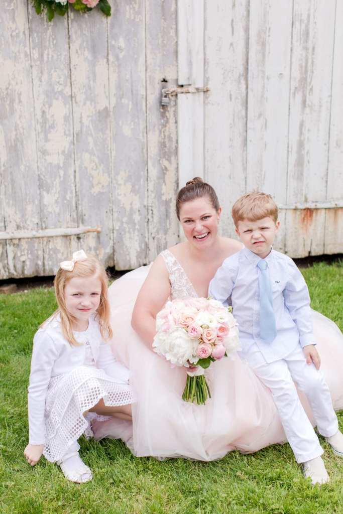 the bride in her blush v-neck gown on the ground with her niece and nephew