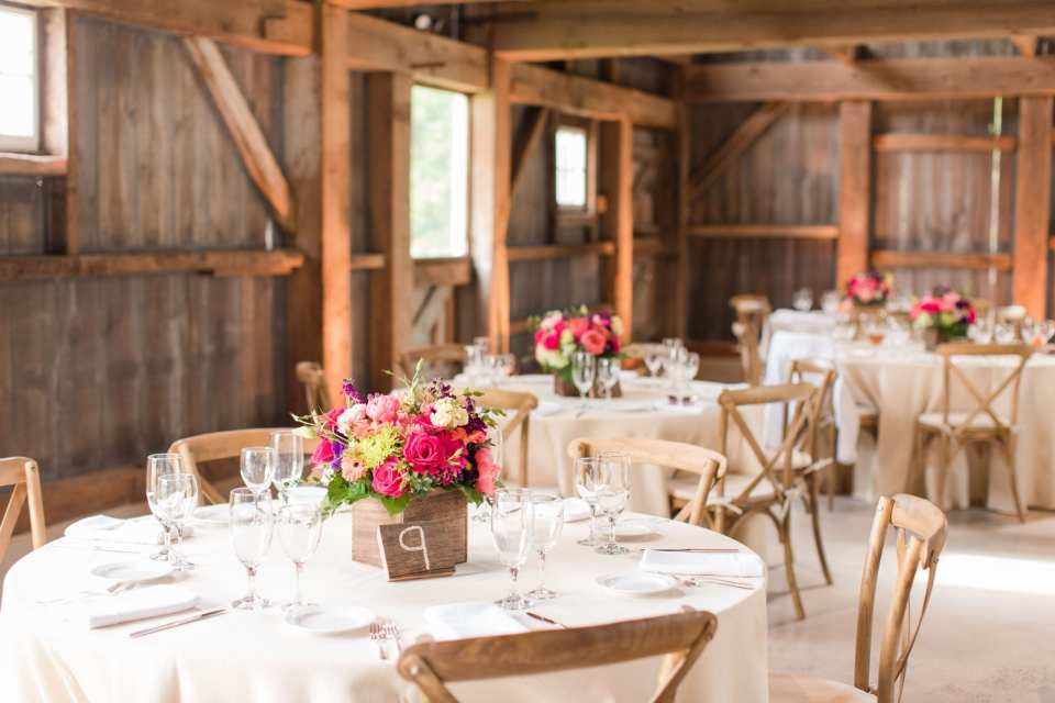 inside the barn reception at the Updike Farmstead where round tables are set up with cream linens, wooden farm chairs and small floral arrangements of multicolored wildflowers, roses, gerber daisies
