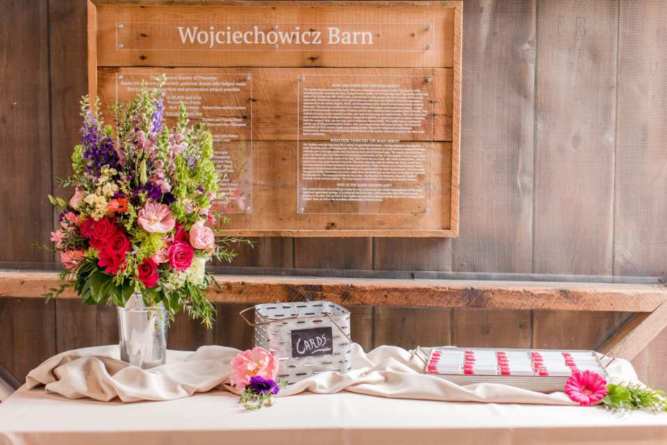 reception details: welcome table inside the barn of the Updike Farmstead that has blush linens, a wildflower and rose floral arrangement, card basket and tray of escort cards