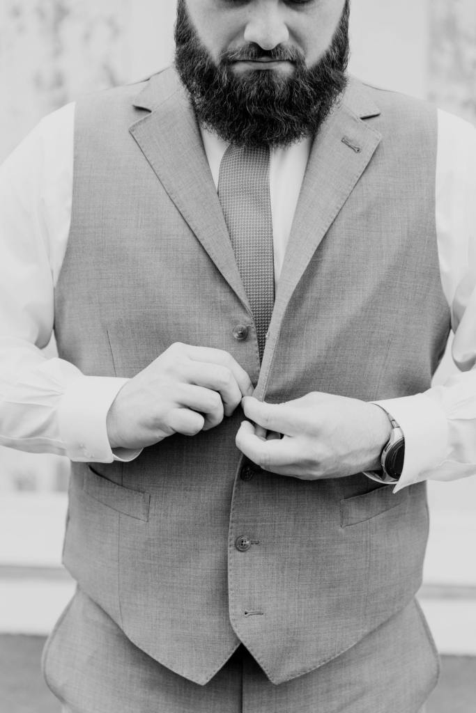black and white photo of the groom buttoning his vest