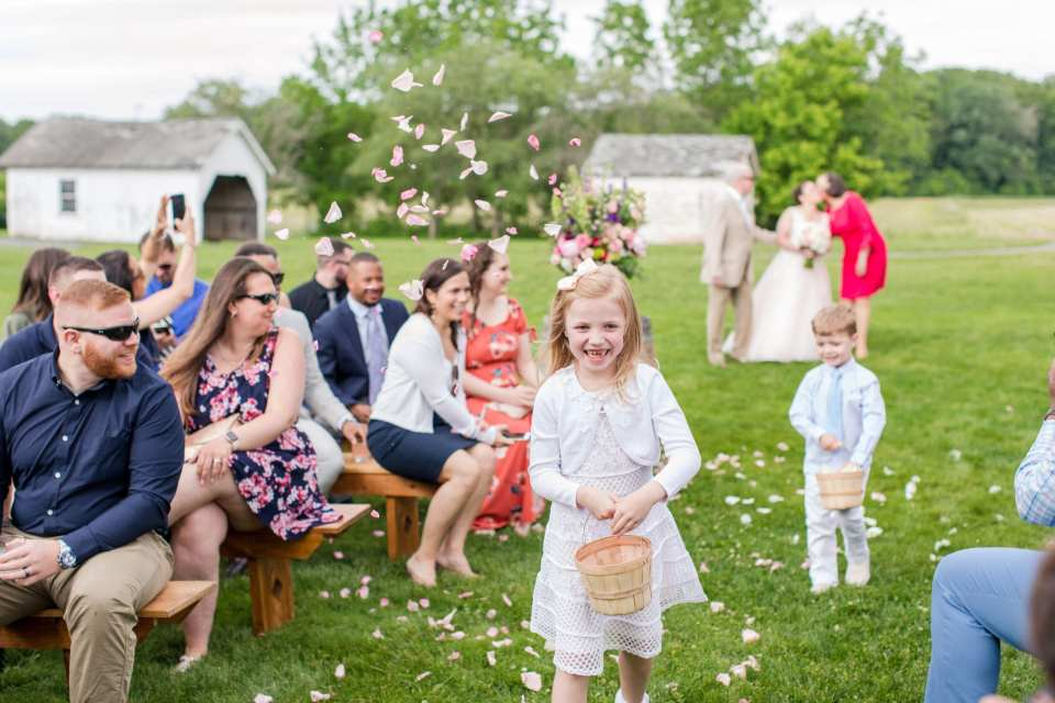 brides niece, a confetti kid or flower girl smiling as she tosses flower petals in the air down the aisle, with her brother following behind