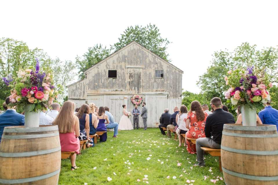 wide angle photo from the end of the aisle during the wedding ceremony with guests sitting on wooden benches, aisle decor of wine barrels topped with wildflower displays, while vows being taken by bride and groom in front of white washed barn decorated with a large floral wreath of cream, pink, blush, and magenta florals at the Updike Farmstead