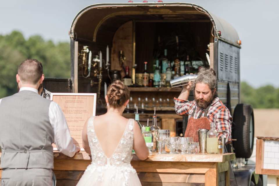 action photo of the bartender from 13th street Cocktails making a drink for the bride and groom at their wooden bar, in front of the horse trailer turned bar