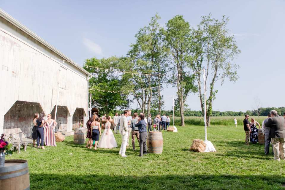 wide angle photo outside of the barn showing the cocktail area with aged barrel tables and guests mingling