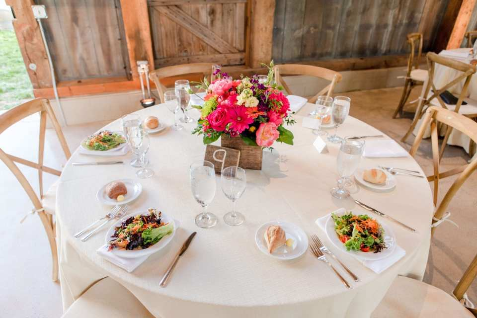 photo of reception table decorated in cream linens with a short wildflower centerpiece and farmhouse style wooden chairs. Each place set with a mixed salad.