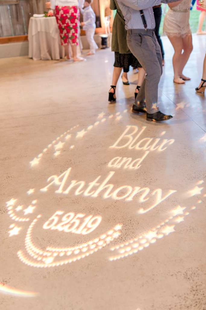 custom gobo on the floor of the barn during the wedding reception with the bride and grooms names and date of wedding