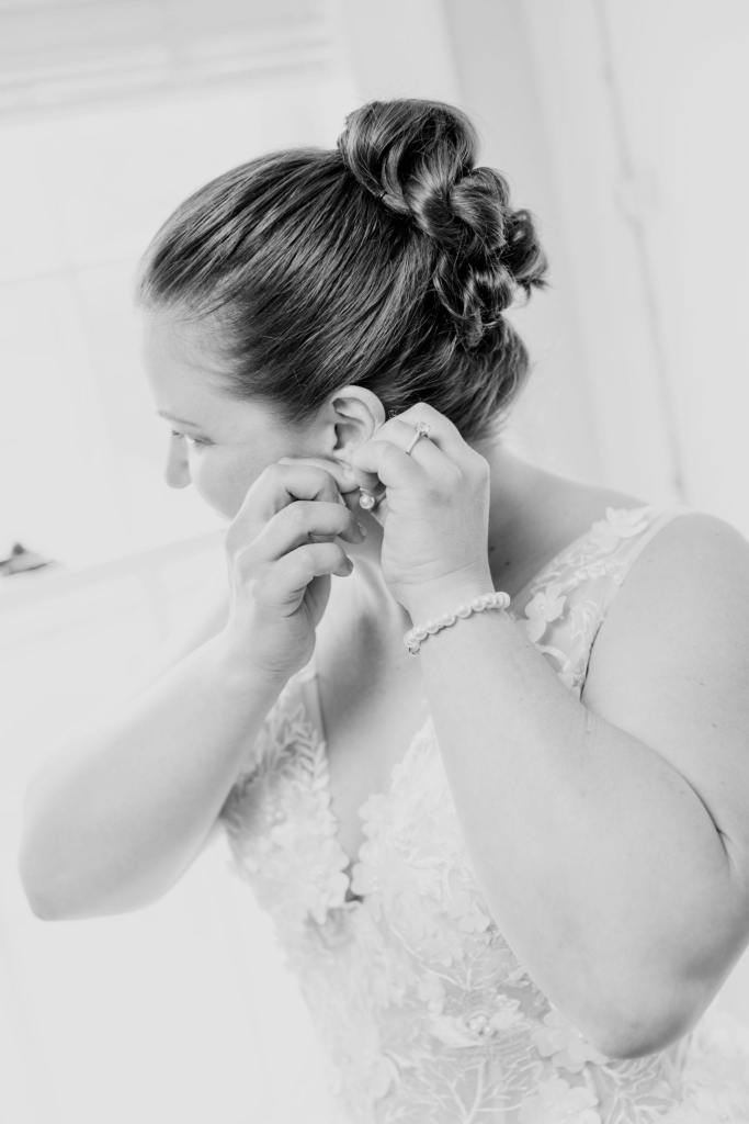 black and white photo of the bride putting in her earring