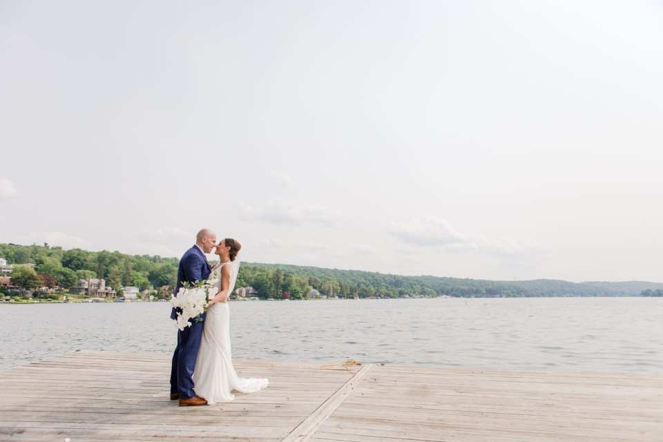 wide angle photo of the lake at Lake Mohawk Country Club with the bride and groom embracing in the lower left quarter of the photo. Bride's gown by Pronovias, Groom in Jos. A. Banks