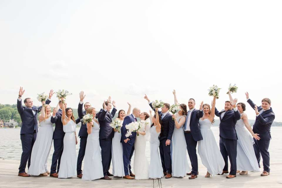 more formal wedding party photo, with all members hands in the air, while standing on either side of the bride and groom against the lake backdrop on the grounds of the Lake Mohawk Country Club. Bridal party is wearing light blue Watters gowns, the groomsmen wearing navy blue suits from Jos. A. Banks