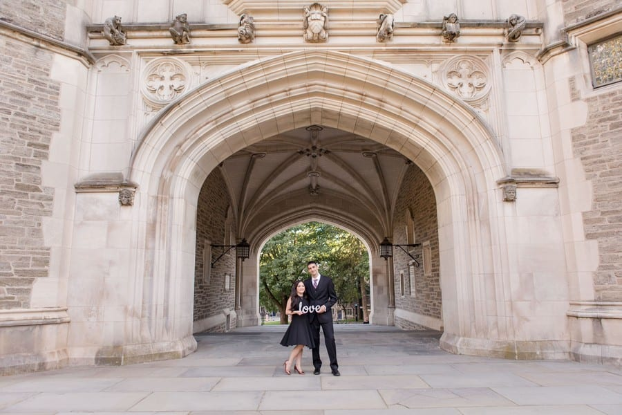 """Bride and groom to be holding a """"love"""" sign, while having their arms wrapped around one another's waist, in front of the archway"""