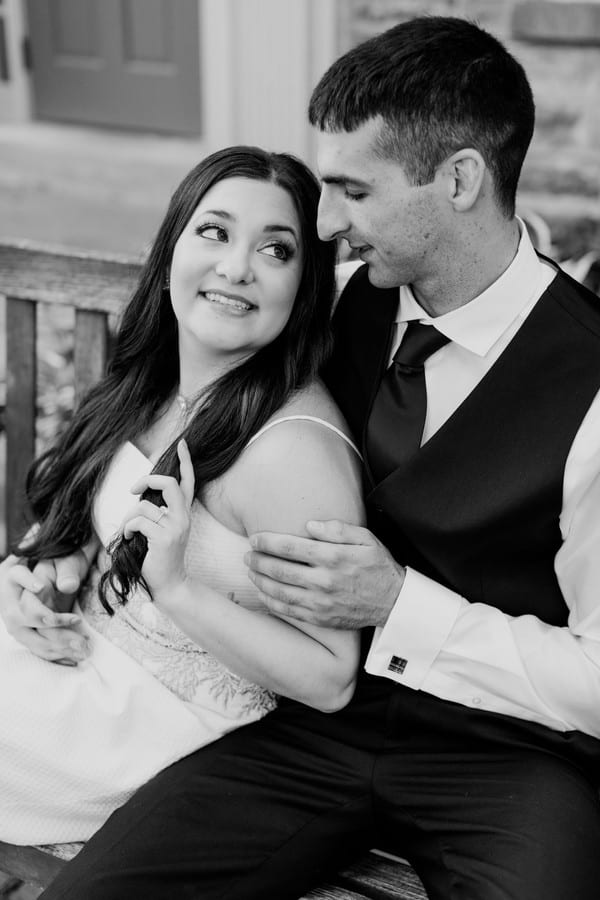 black and white image of the bride to be and her fiance sitting on a bench. She has her hair in one hand, while leaning against him, while he sits and holds her with his left arm on her left arm
