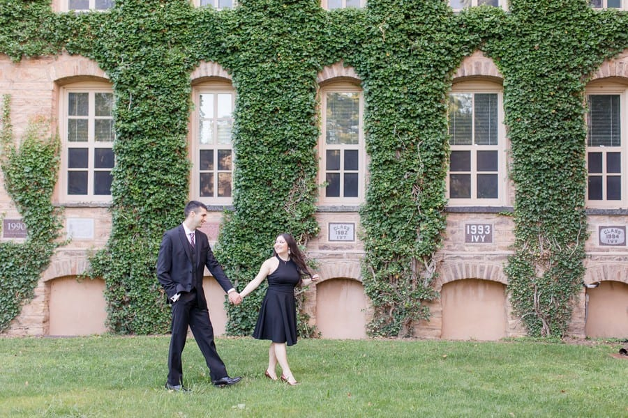 Bride to be dressed in a short black sleeveless dress by Aqua, leading her groom to be, dressed in a 3 piece black suit by Calvin Klein, with one hand while walking behind the ivy covered Nassau Hall building on the campus of Princeton University