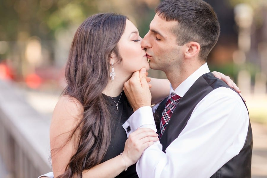 Bride to be sitting in the lap of the groom to be, kissing him. She is wearing a black sleeveless dress by Aqua, he is wearing a 3 piece black suit by Calvin Klein, without the jacket.