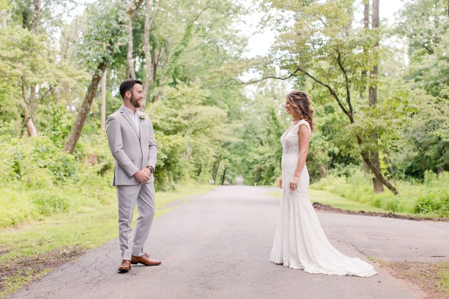 a wide angle photo of the bride and groom looking and smiling at one another during their first look. Her gown by Calla Blanche, his suit by Generation Tux