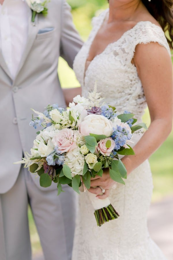 a 3/4 shot of the bride and groom with their arms around one another, the brides bouquet of white, pink and light blue florals in focus