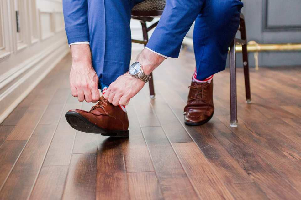 Groom putting on his brown shoes