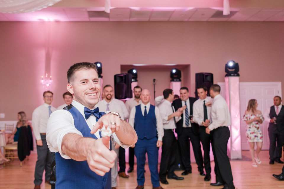 the groom poses with garter, as if he's going to shoot it at the camera, while the men gather in the background to try and catch it