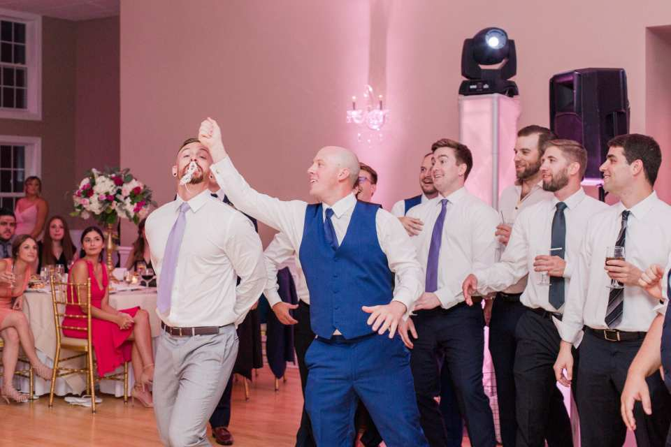 The men try to catch the tossing of the garter during the reception