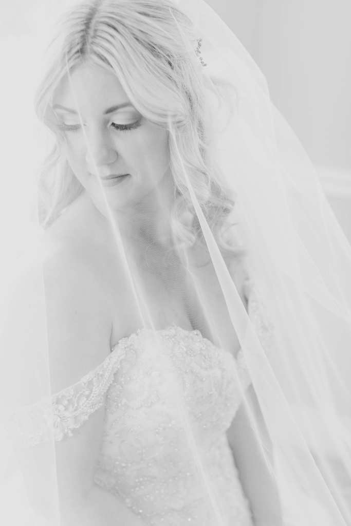 Black and white portrait of the bride under her veil