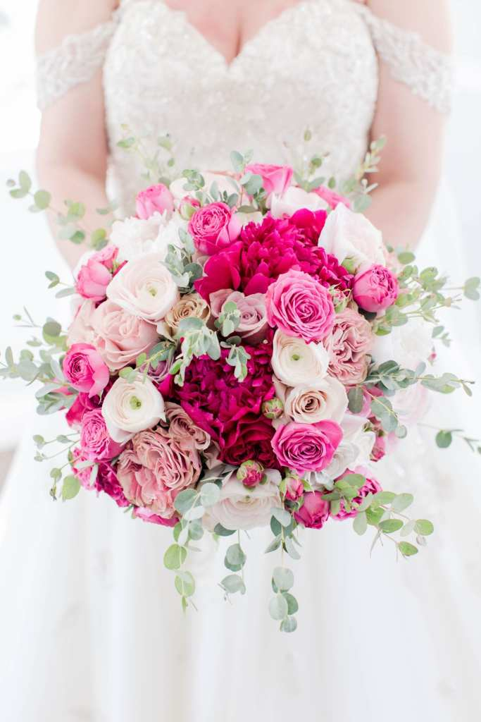 close up of the bride holding her bridal bouquet at her waist. Bouquet is comprised of florals in varying shades of pink and white, with eucalyptus, by Pink Dahlia Events