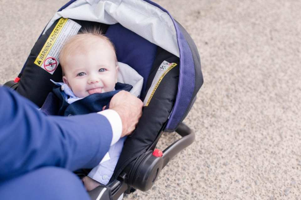 baby boy smiling and sticking out his tongue while in his baby carrier