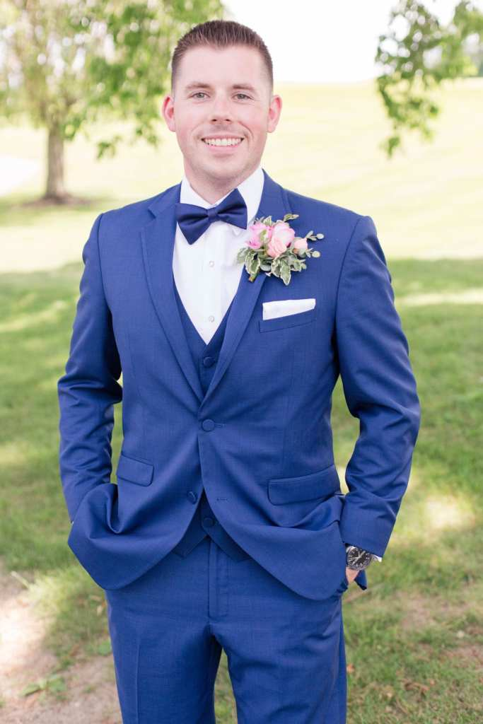 Formal portrait of the groom in a navy blue tuxedo by the Clothing Center