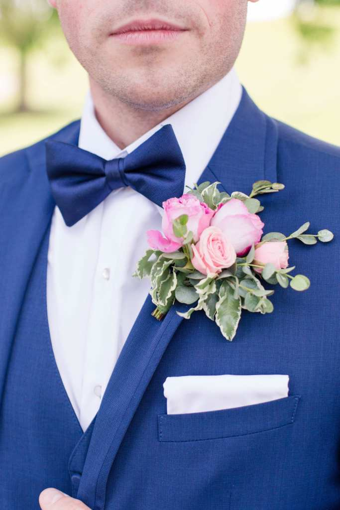 Close up photo of the boutonniere of the groom. Pink florals with greens by Pink Dahlia Events