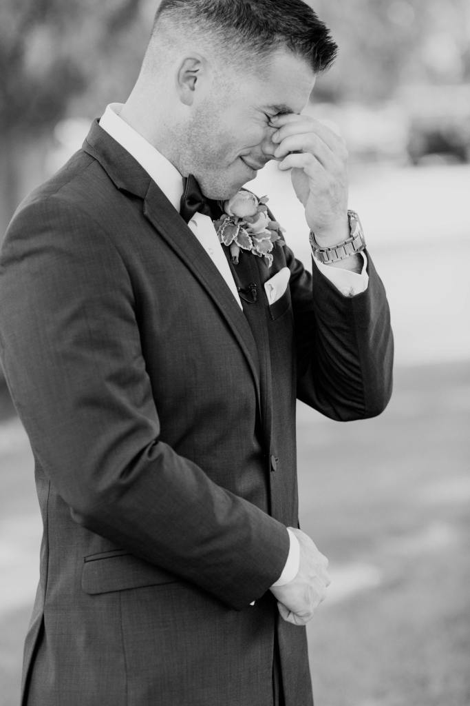 Black and white candid photo of the groom shedding a tear during the first look