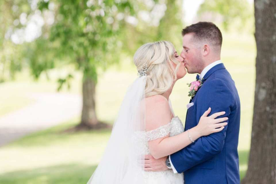 Wide angle shot of the bride and groom kissing during the first look
