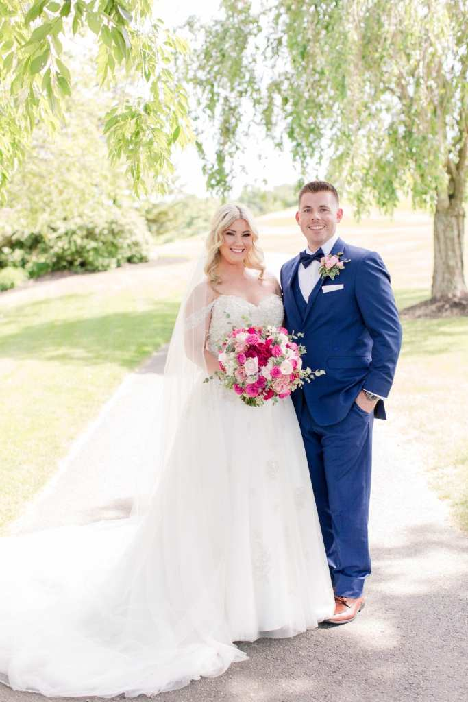 Formal full length portrait of the bride and groom on the golf cart path at Skyview Golf Club. Bride in Justin Alexander, groom in a navy blue tuxedo by the Clothing Center