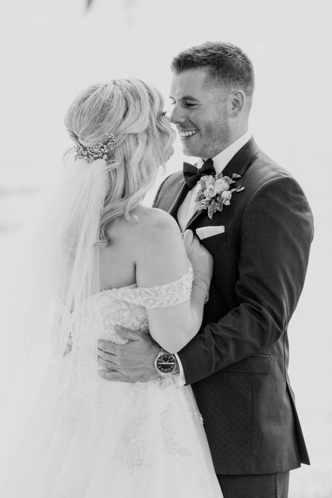 Black and white photo of the groom holding his bride at her waist while smiling at her, her back angled towards the camera