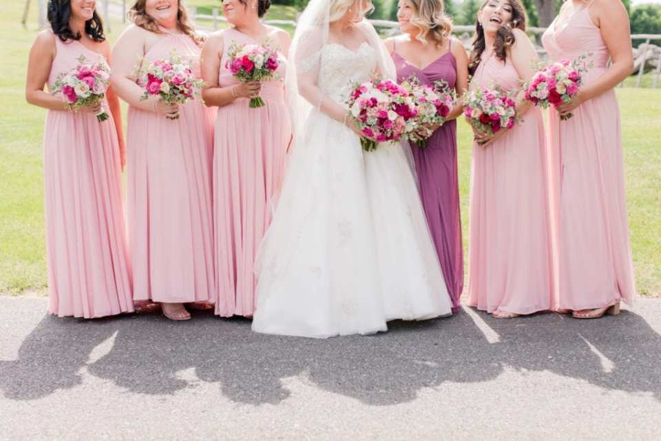 informal photo focusing on the gowns of the bride, by Justin Alexander, and her bridal party, in pinks by David's Bridal. Bouquets of pink and white florals by Pink Dahlia Events