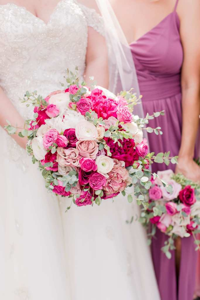 the bride and maid of honor 3/4 photo with their bouquets of pink florals in varying shades, along with white florals and greenery by Pink Dahlia Events