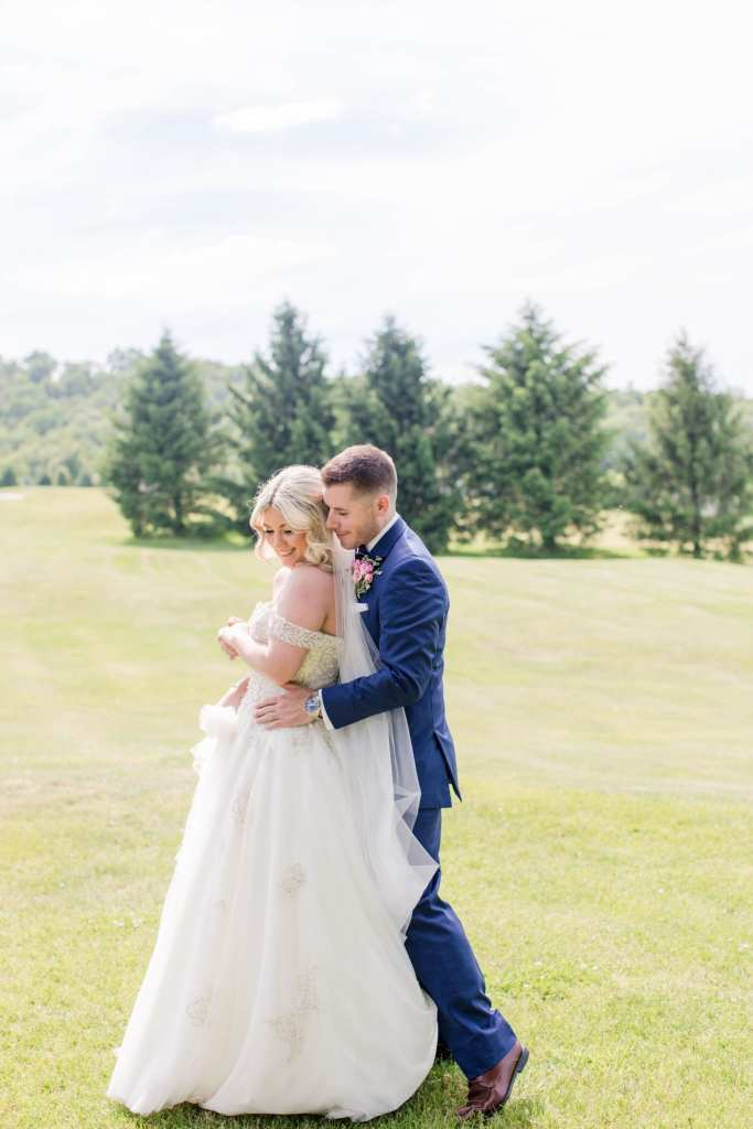 fun portrait of the bride and groom on the golf course, groom with his arms wrapped around the brides waist