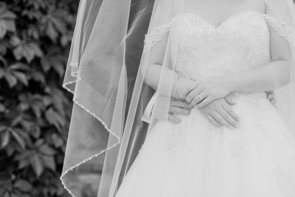 black and white photo of the grooms hands around the waist of the bride. Bridal gown by Justin Alexander