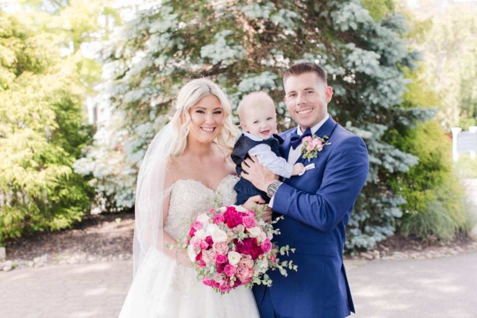 Bride and groom portrait with young boy. Brides bouquet of various florals in shades of pink and white with greenery by Pink Dahlia Events