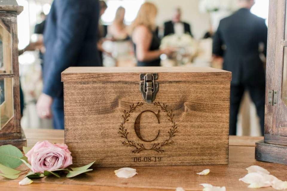 """a photo of the wooden card box with a """"C"""" carved into it along with the date of the wedding"""