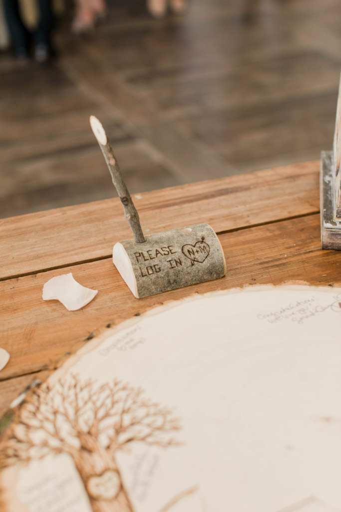 a photo of the wooden pen in a stand the guests use to sign the custom wooden guest book