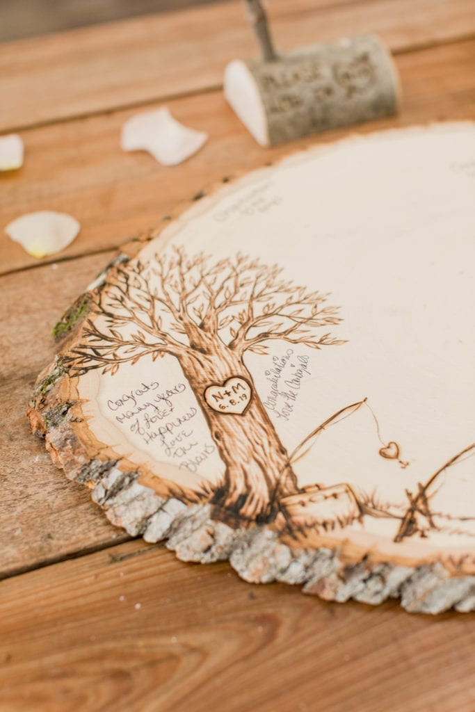 A photo of a slice from a tree engraved with a drawing of a tree and the bride and grooms initials and date of their wedding that is being signed by guests as a unique guest book