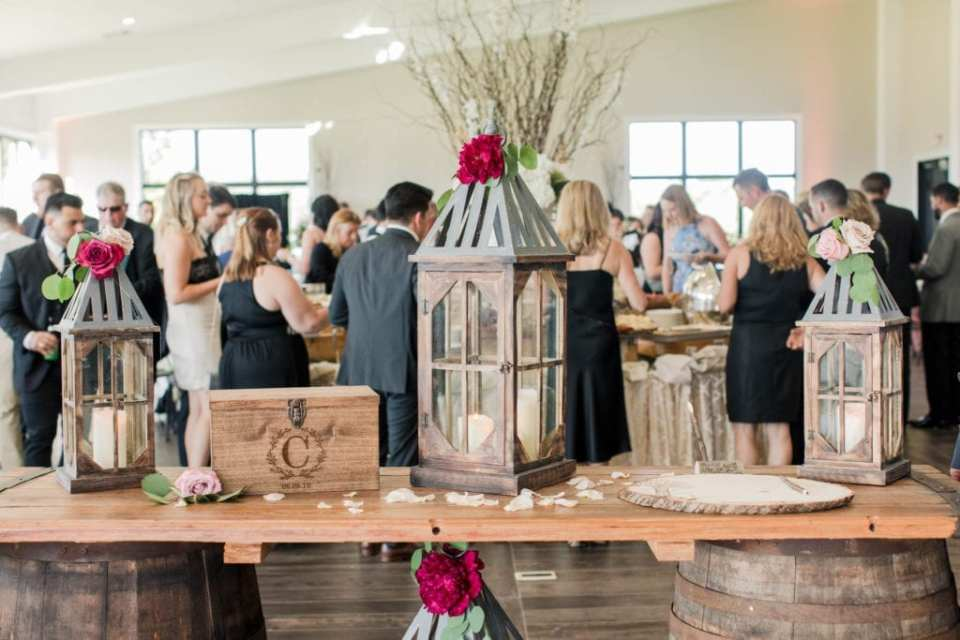 details during the cocktail hour including a wooden plank on top of wine barrels with wooden glass candle boxes and a wooden box with the monogram of the bride and groom and the date of their wedding