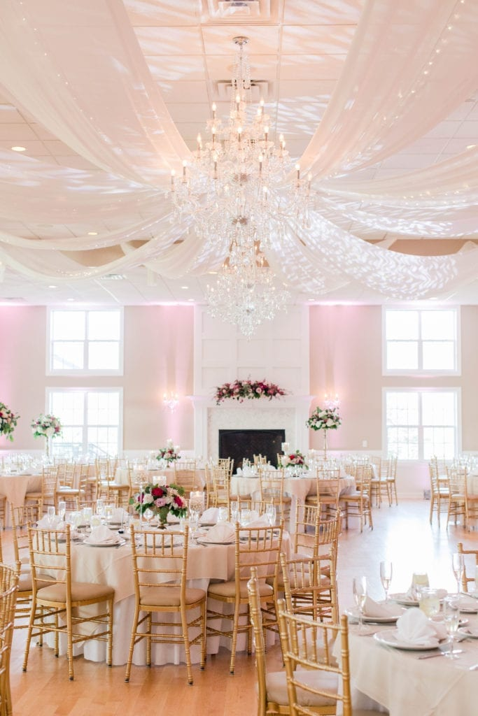 a vertical photo of the ballroom at the Skyview Golf Club with ceiling drapery, crystal chandelier, tables set with white linens, both low and tall floral arrangements and gold chivari chairs