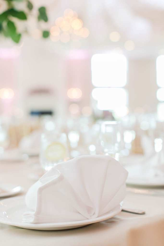 focus on a white napkin folded accordion style on a white plate on a table in the reception area