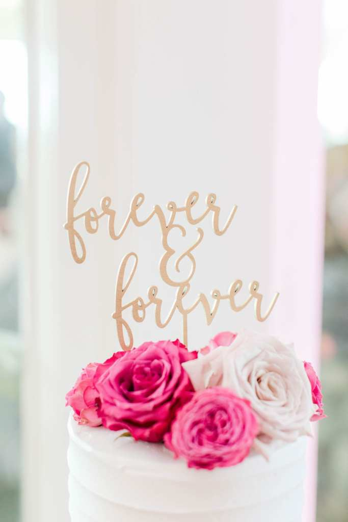 "the gold cake topper saying ""forever & forever"" atop the white wedding cake with pink and white roses"