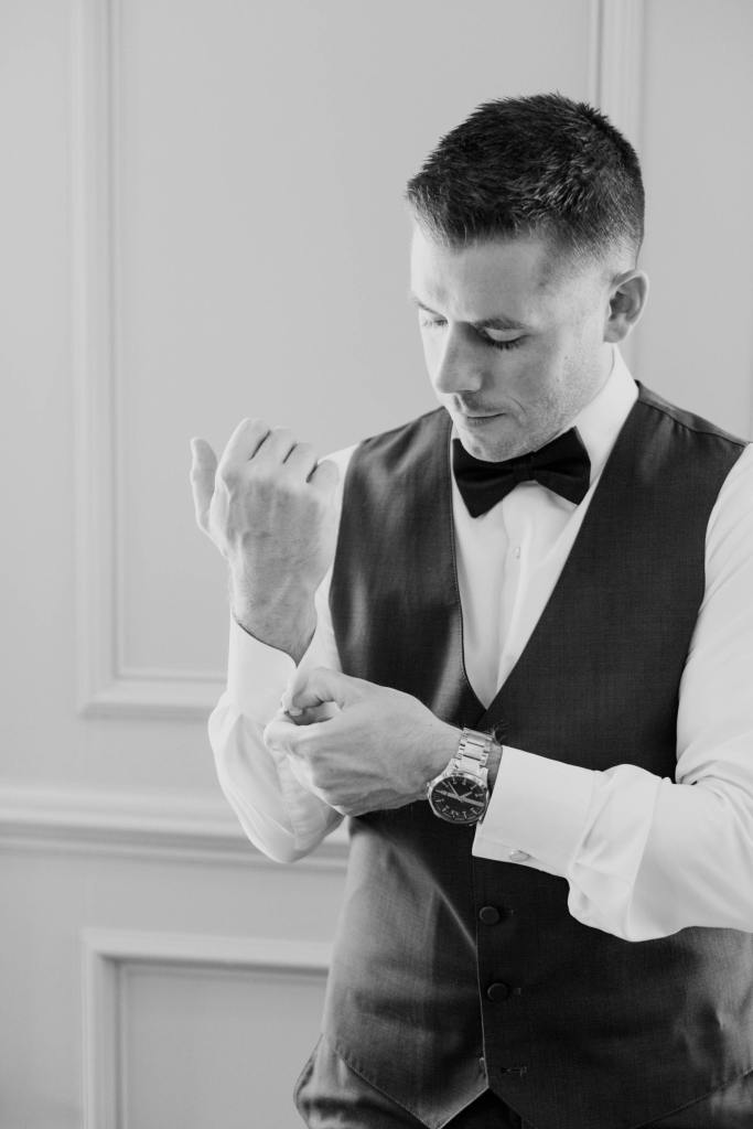 Black and white candid photo of the groom putting on his cufflinks