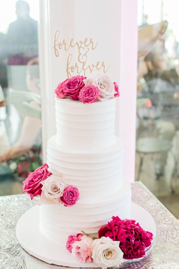 the three tier white wedding cake by a Little Cake with pink and white florals, topped with a gold forever & forever cake topper