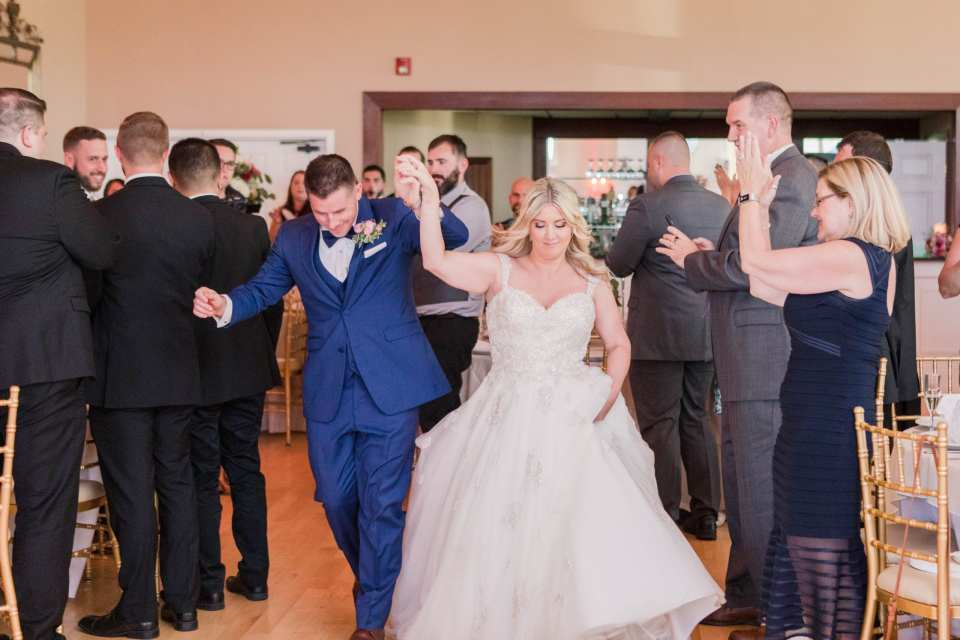 the bride and groom holding their hands in the air while making their entrance into the reception
