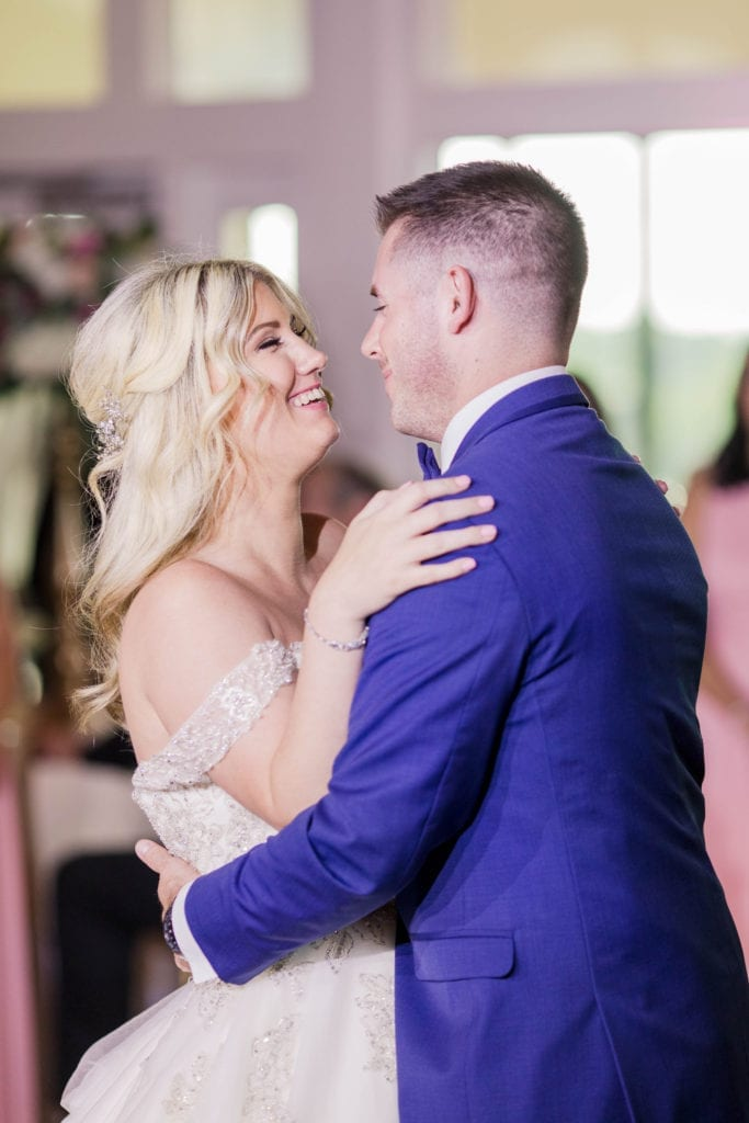 a 3/4 shot from the side of the bride and groom smiling at one another while dancing their first dance
