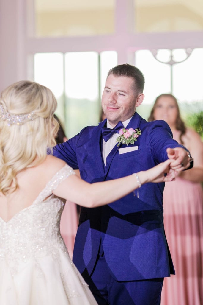 the bride and groom dancing their first dance, focus on the groom